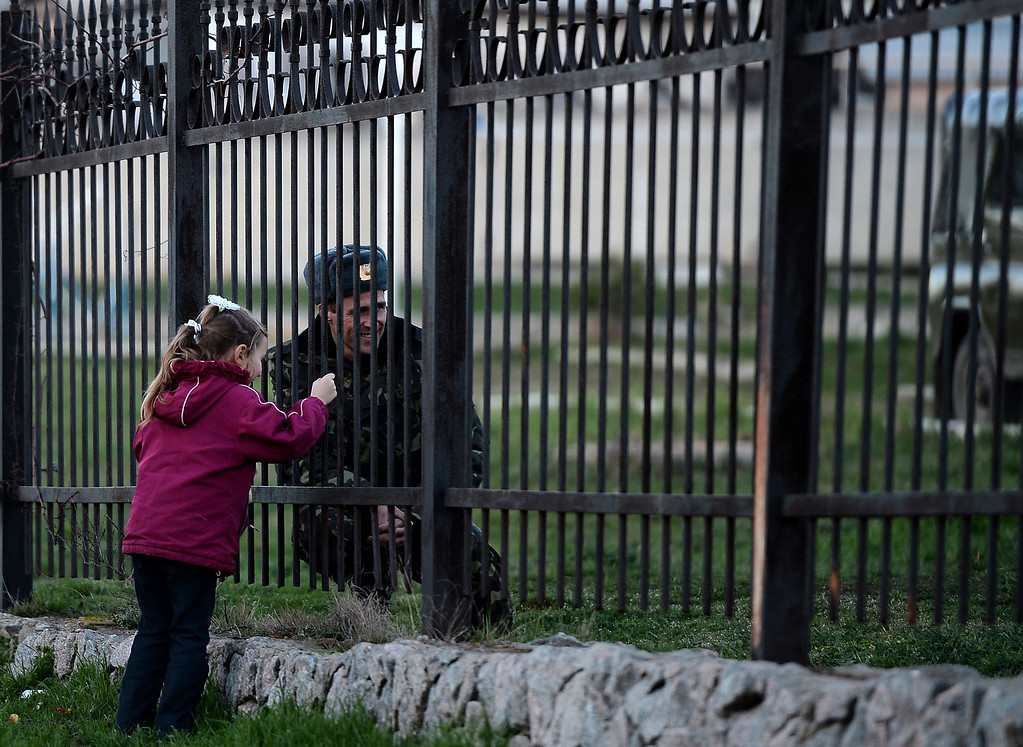 . A Ukrainian soldier speaks to his daughter through a gate as he waits inside the Sevastopol tactical military brigade base near Belbek in Sevastopol on March 3, 2014. AFP PHOTO / FILIPPO MONTEFORTE/AFP/Getty Images