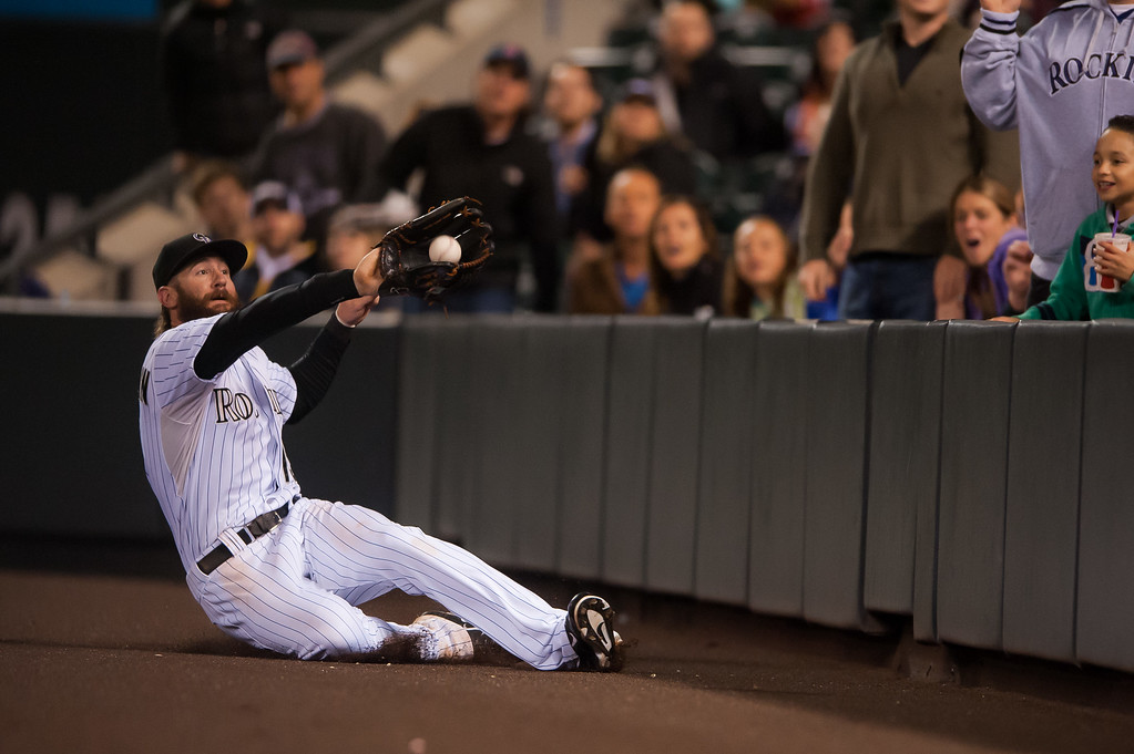. DENVER, CO - SEPTEMBER 05:  Charlie Blackmon #19 of the Colorado Rockies makes a sliding catch in foul territory for an eighth inning out against the San Diego Padres at Coors Field on September 5, 2014 in Denver, Colorado.  (Photo by Dustin Bradford/Getty Images)
