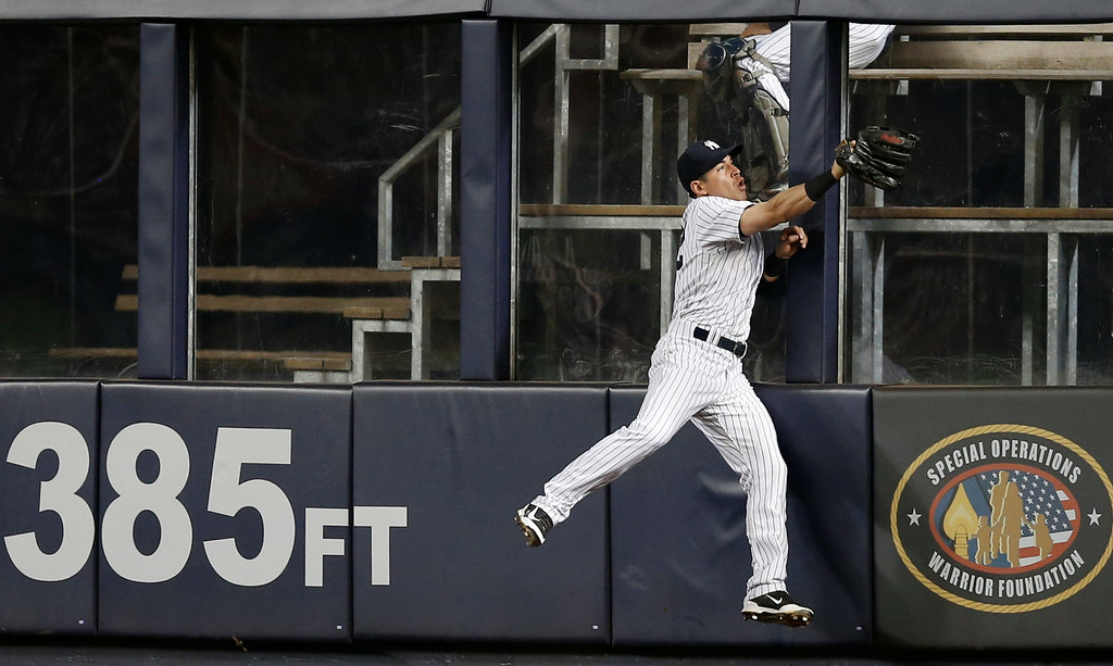 . New York Yankees center fielder Jacoby Ellsbury (22) leaps fielding a sixth-inning fly out hit by Detroit Tigers J.D. Martinez in a baseball game at Yankee Stadium in New York, Wednesday, Aug. 6, 2014.  (AP Photo/Kathy Willens)