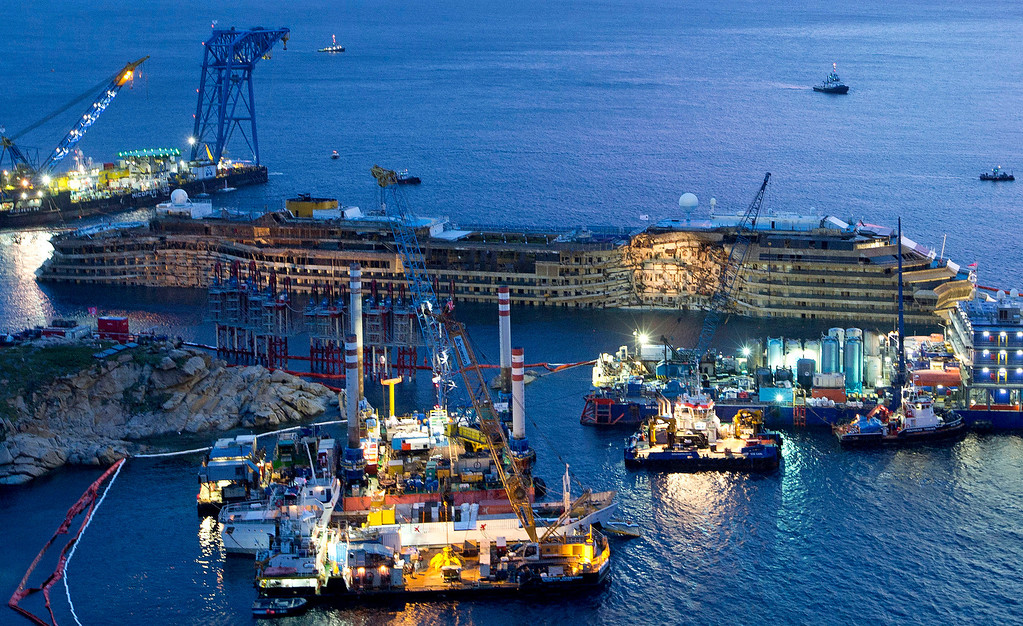 ". The Costa Concordia is seen after it was lifted upright, on the Tuscan Island of Giglio, Italy, early Tuesday morning, Sept. 17, 2013. The crippled cruise ship was pulled completely upright after a complicated, 19-hour operation to wrench it from its side where it capsized last year off Tuscany, with officials declaring it a ""perfect\"" end to a daring and unprecedented engineering feat. (AP Photo/Andrew Medichini, File)"