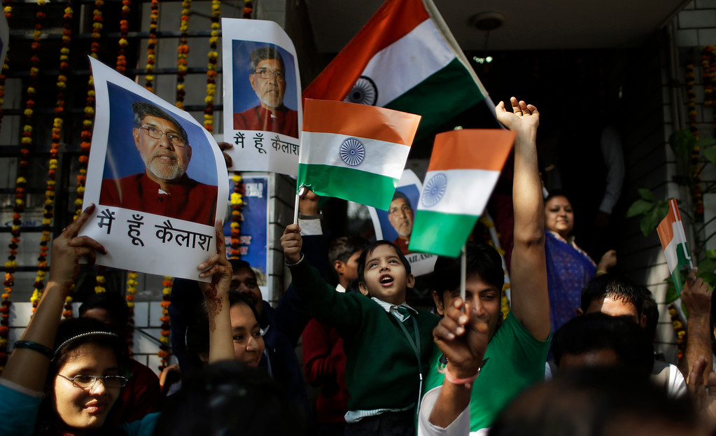 """. Workers and rescued child laborers at the Bachpan Bachao Andolan, or Save the Children Movement, founded by Indiaís Nobel laureate Kailash Satyarthi wave the Indian flag and display Satyarthi\'s photographs as they celebrate at the organizationís office in New Delhi, India, Wednesday, Dec. 10, 2014. Satyarthi who split the $1.1 million Peace Prize, with Pakistanís Malala Yousafzai will be conferred the award at a ceremony in Oslo on Wednesday. Hindi reads, \""""I am Kailash\"""".(AP Photo/Altaf Qadri)"""