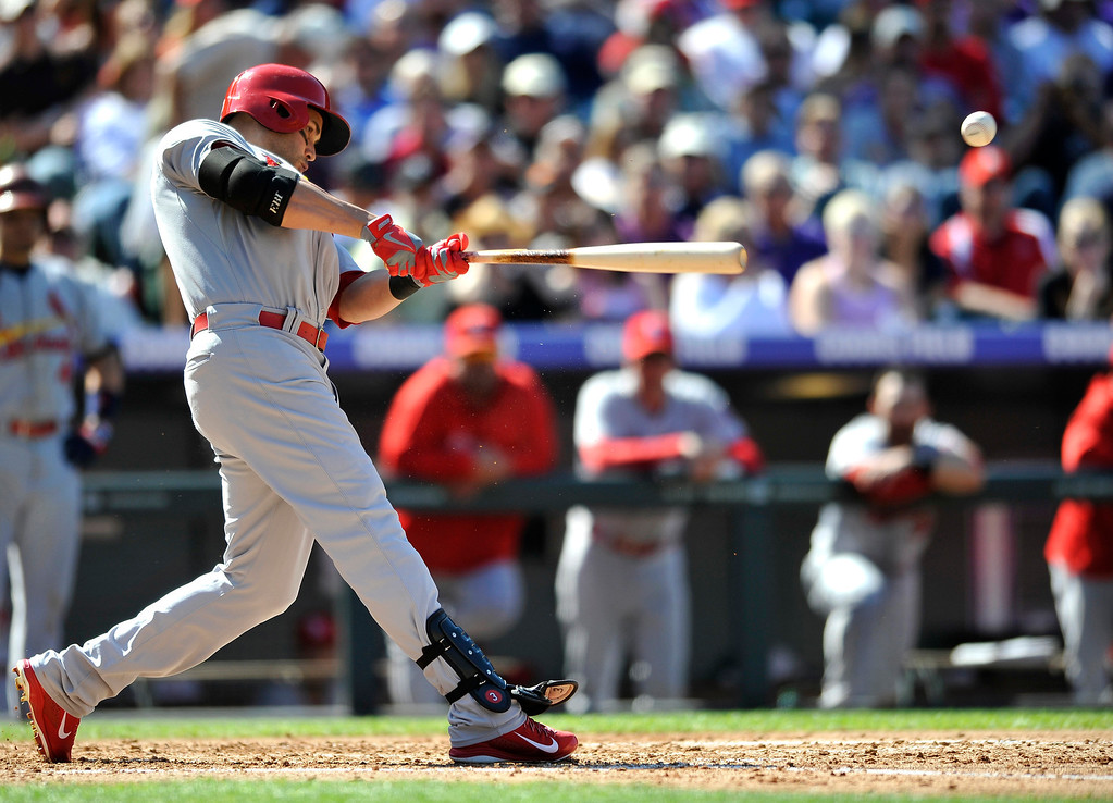 . St. Louis Cardinals\' Carlos Beltran hits an RBI single against Colorado Rockies starting pitcher Roy Oswalt during the fourth inning of a baseball game on Thursday, Sept. 19, 2013, in Denver. (AP Photo/Jack Dempsey)