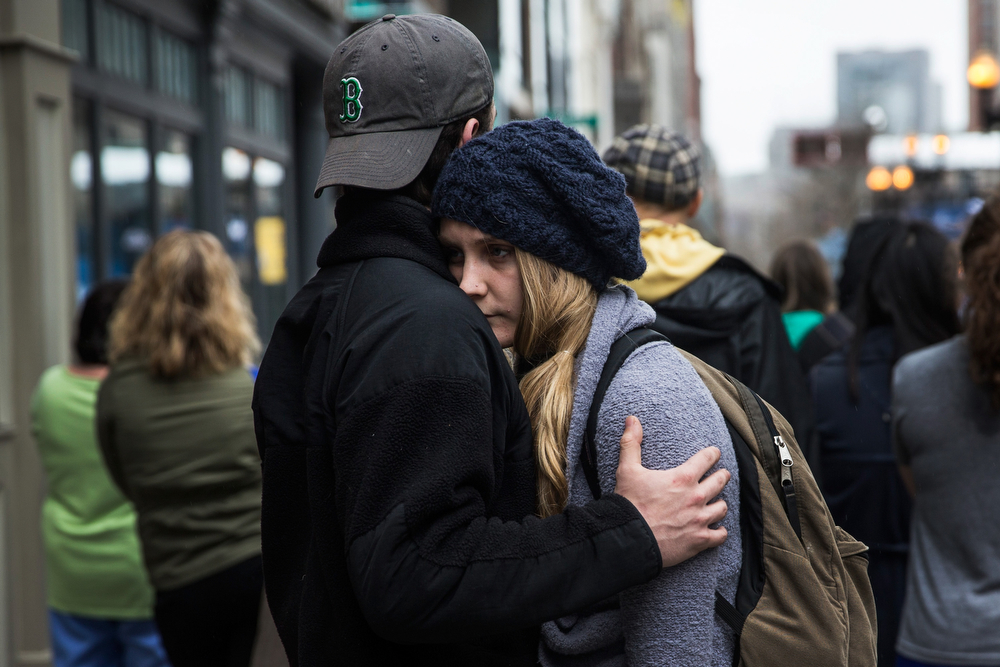. Tom Duggan hugs Sarah Rogo, who said they were both present last year at the marathon, while a billboard television screen broadcasts the ceremony commemorating the one year anniversary of the 2013 Boston Marathon Bombing , on April 15, 2014 in Boston, Massachusetts. Last year, two pressure cooker bombs killed three and injured an estimated 264 others during the Boston marathon, on April 15, 2013. Neary says she was standing near the site of the bombing before it went off.  (Photo by Andrew Burton/Getty Images)