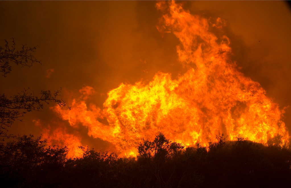 . Flames from a massive wildfire burn Monday, Oct. 9, 2017, in Napa, Calif. (AP Photo/Rich Pedroncelli)