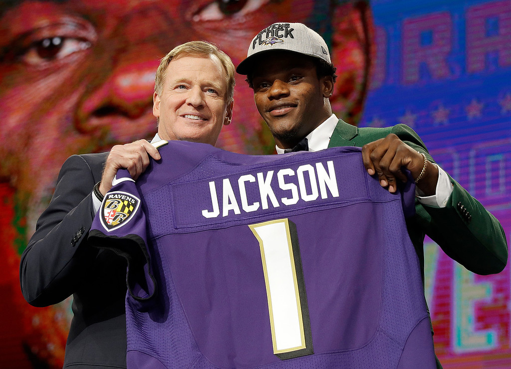 . Commissioner Roger Goodell, left, presents Louisville\'s Lamar Jackson with his Baltimore Ravens jersey during the first round of the NFL football draft, Thursday, April 26, 2018, in Arlington, Texas. (AP Photo/David J. Phillip)