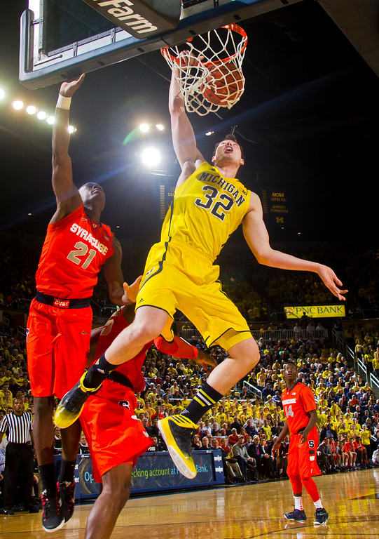 . Michigan forward Ricky Doyle (32) dunks the ball, with Syracuse forward Tyler Roberson (21) defending, in the second half of an NCAA college basketball game at Crisler Center in Ann Arbor, Mich., Tuesday, Dec. 2, 2014. Michigan won 68-65. (AP Photo/Tony Ding)
