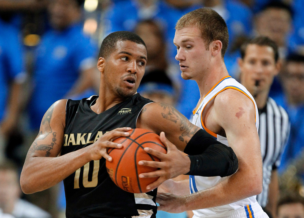 . Oakland guard Duke Mondy, left, takes the ball around UCLA guard Bryce Alford during the second half of an NCAA college basketball game Tuesday, Nov. 12, 2013, in Los Angeles. UCLA won 91-60. (AP Photo/Alex Gallardo)