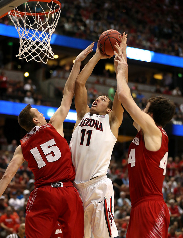 . Aaron Gordon #11 of the Arizona Wildcats goes up for a shot against Sam Dekker #15 and Frank Kaminsky #44 of the Wisconsin Badgers in the second half during the West Regional Final of the 2014 NCAA Men\'s Basketball Tournament at the Honda Center on March 29, 2014 in Anaheim, California.  (Photo by Jeff Gross/Getty Images)