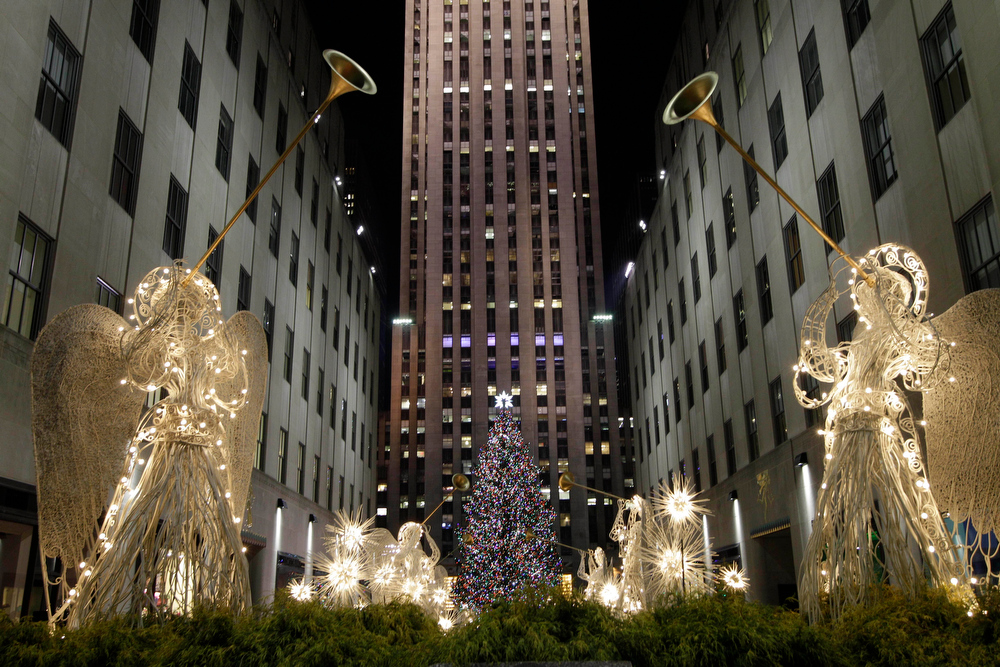Description of . Angels decorations frame the Rockefeller Center Christmas tree after it was lit during the 80th annual tree lighting ceremony at Rockefeller Center in New York, Wednesday, Nov. 28, 2012.  (AP Photo/Kathy Willens)