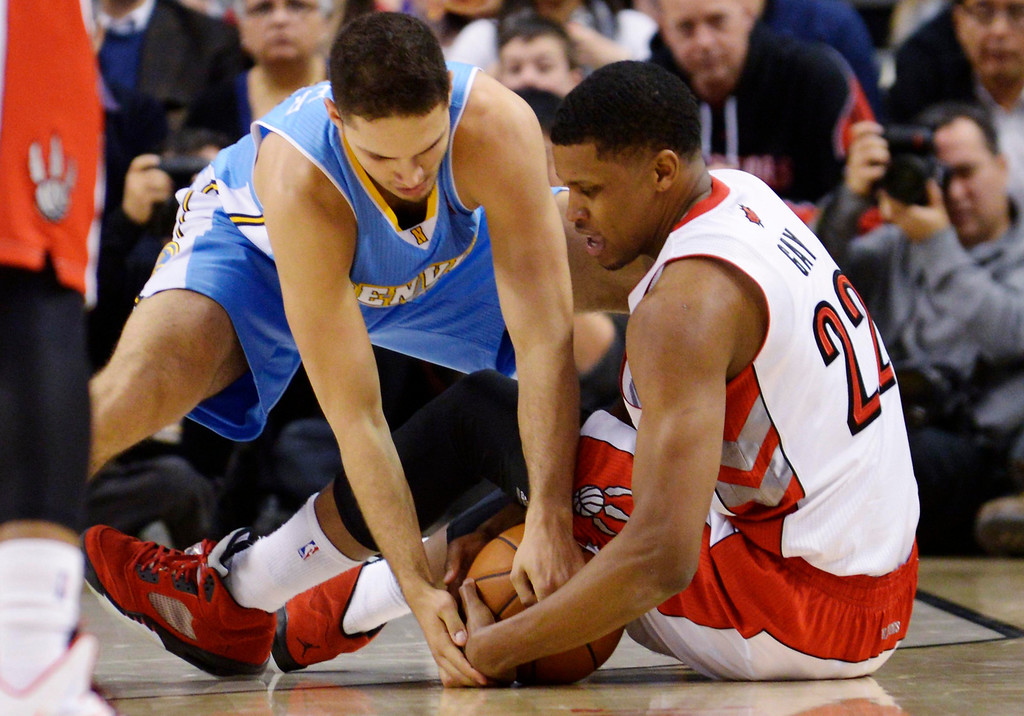 . Toronto Raptors Rudy Gay fights for a loose ball against Denver Nuggets\' Evan Fournier during the second half of their NBA basketball game in Toronto February 12, 2013.  REUTERS/Jon Blacker