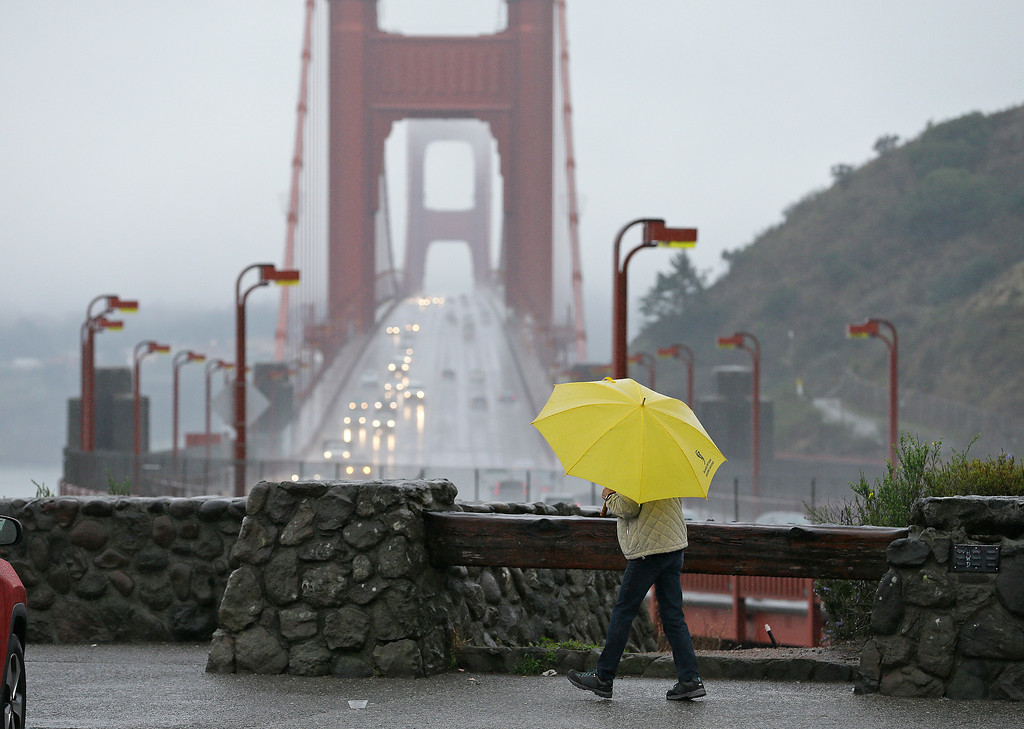 . A woman walks in the rain at a vista point with the Golden Gate Bridge in the background Monday, Jan. 8, 2018, near Sausalito, Calif. Storms brought rain to California on Monday and increased the risk of mudslides in fire-ravaged communities in devastated northern wine country and authorities to order evacuations farther south for towns below hillsides burned by the state\'s largest-ever wildfire. (AP Photo/Eric Risberg)