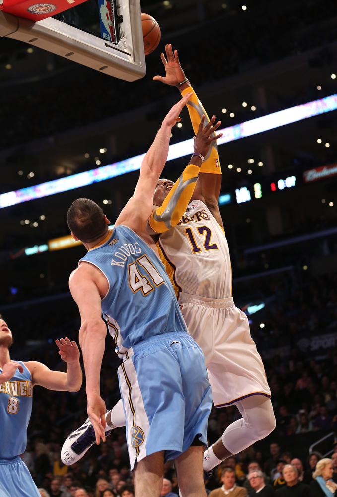 Description of . Dwight Howard #12 of the Los Angeles Lakers shoots over Kosta Koufos #41 of the Denver Nuggets at Staples Center on January 6, 2013 in Los Angeles, California.   (Photo by Stephen Dunn/Getty Images)
