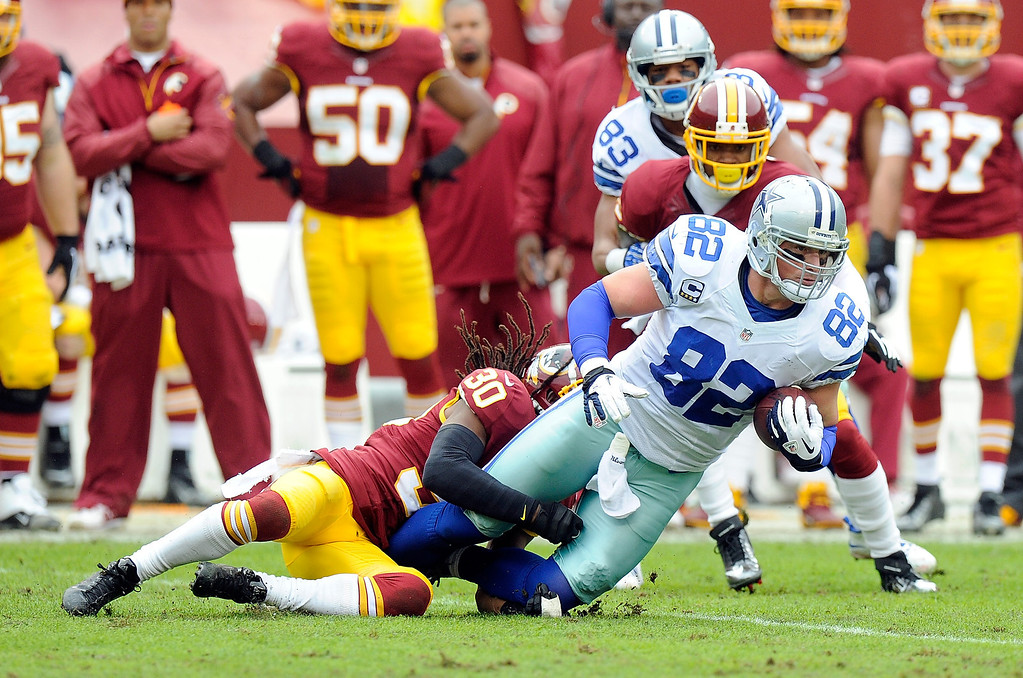 . Jason Witten #82 of the Dallas Cowboys is tackled in the first quarter by E.J. Biggers #30 of the Washington Redskins at FedExField on December 22, 2013 in Landover, Maryland.  (Photo by Greg Fiume/Getty Images)