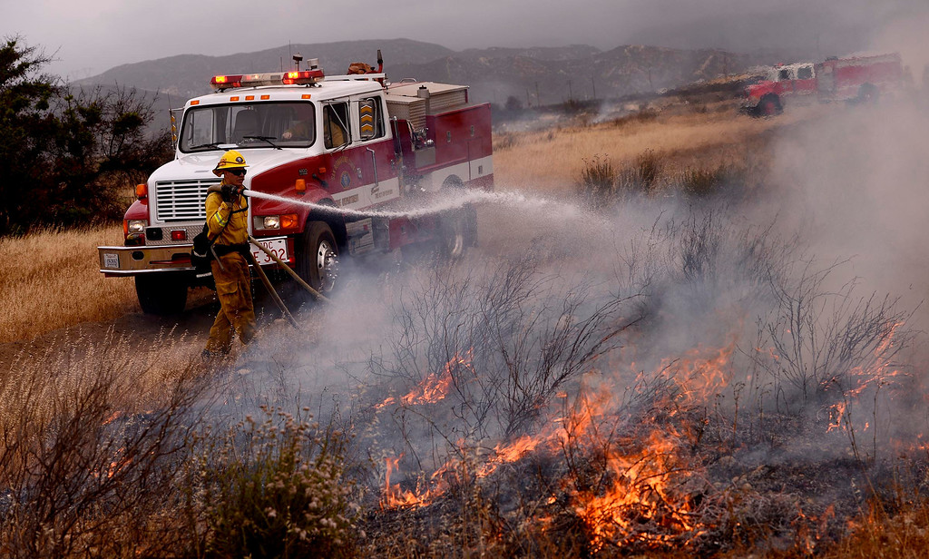 . A firefighter hoses down a section of burning vegetation during a training fire along Sierra Avenue north of Summit Avenue in North Fontana May 23, 2013.   GABRIEL LUIS ACOSTA/STAFF PHOTOGRAPHER.