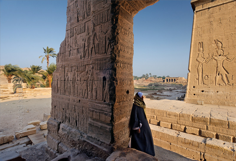 [EGYPT 29511] 'Isis Temple at Dendera.'  A temple guard is resting against the porch of the Isis Temple at Dendera. The Isis Temple (built in the 1st century AD) is a separate building located south of the main temple, which is dedicated to Hathor. The southern exterior wall of the Hathor Temple can be seen on the right, with reliefs of the famous Queen Cleopatra VII and her son pharaoh Ptolemy XV (Caesarion). On the left we see the grove of palms which rises from the bottom of the sacred lake. Photo Mick Palarczyk.