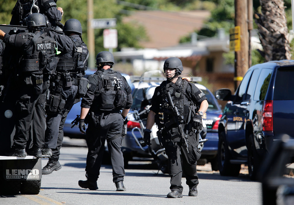 . Members of the San Jose Police Depart MERGE unit begin to search the neighborhood at Diana Lane and Story Rd. for a gunman who tried to rob a check-cashing store in East San Jose, Calif. on Thursday, Aug. 1, 2013.  (Gary Reyes/Bay Area News Group)