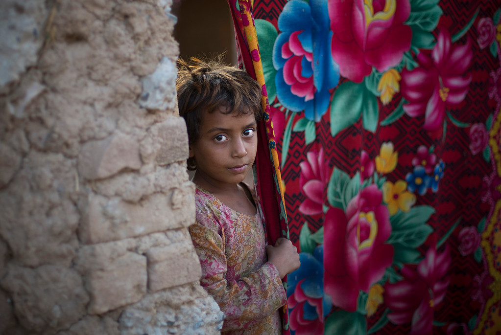 . A girl, who is displaced from Pakistani tribal area due to security forces\' crackdown operation against militants, looks out from  her mud house living under a poverty line in suburbs of Islamabad, Pakistan, Friday, Oct 17, 2014. (AP Photo/B.K. Bangash)