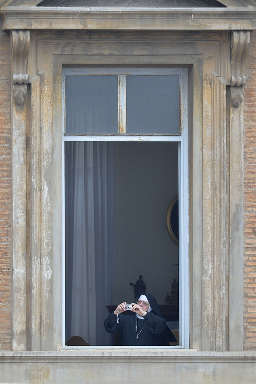 . A nun takes a picture from a window before the canonisation mass of Popes John XXIII and John Paul II at the Vatican on April 27, 2014.  Catholics from around the world gathered in Rome on Sunday for a mass presided by Pope Francis to confer sainthood on John Paul II and John XXIII -- two influential popes who helped shape 20th century history.  AFP PHOTO / ANDREAS SOLAROPeople take their seats to attend the canonisation mass of Popes John XXIII and John Paul II at the Vatican on April 27, 2014.  Catholics from around the world gathered in Rome on Sunday for a mass presided by Pope Francis to confer sainthood on John Paul II and John XXIII -- two influential popes who helped shape 20th century history.  AFP PHOTO / ANDREAS SOLARO