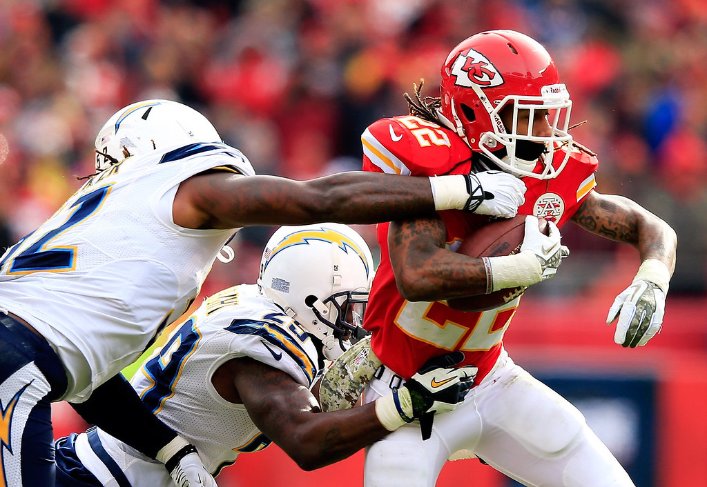 . Wide receiver Dexter McCluster #22 of the Kansas City Chiefs carries the ball as inside linebacker Reggie Walker #52 and cornerback Shareece Wright #29 of the San Diego Chargers defend during the game at Arrowhead Stadium on November 24, 2013 in Kansas City, Missouri.  (Photo by Jamie Squire/Getty Images)