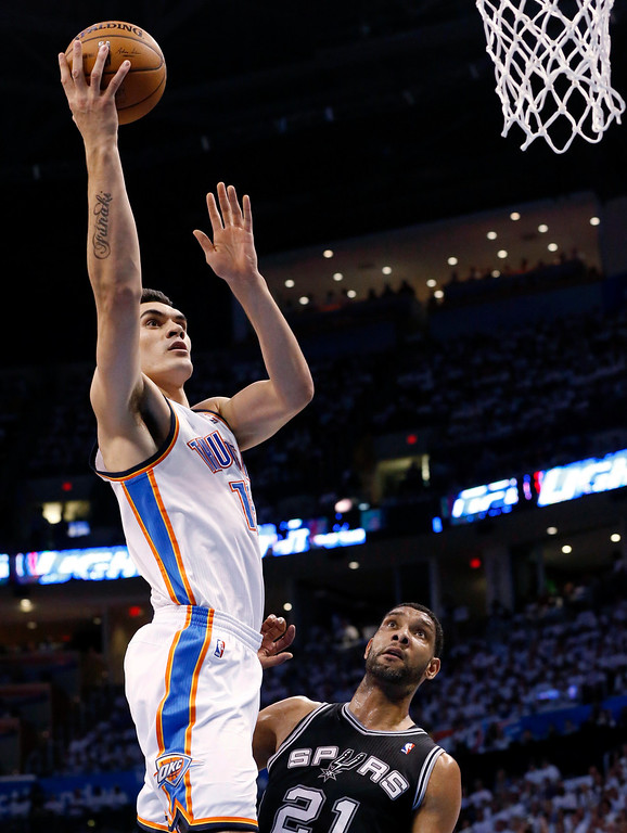 . Oklahoma City Thunder center Steven Adams shoots over San Antonio Spurs forward Tim Duncan (21) during the first half of Game 6 of the Western Conference finals NBA basketball playoff series, in Oklahoma City, Saturday, May 31, 2014. (AP Photo/Sue Ogrocki)