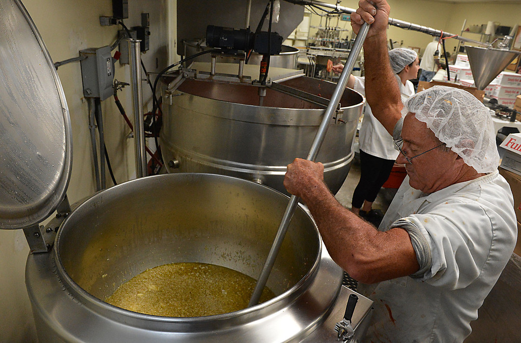 . Gary Hummel stirs a cooking batch of olive oil, onions and garlic while cooking Saverino\'s Marinara Sauce at Da\'Kine Foods in Newport Beach. Following the successful launch of Saverino\'s Italian Deli and Market in Redlands nearly two years ago, David Saverino is bottling the flavor of his business with the introduction of four separate sauces. In addition to selling the sauces at his deli, Saverino hopes to see his product on the shelves of local markets. (Photo by Rick Sforza/Redlands Daily Facts)