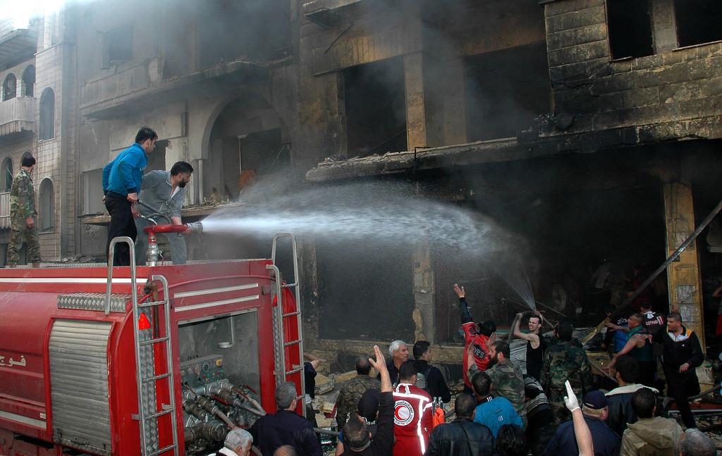 . Emergency services spray water on a building following a car bomb explosion in al-Khudary Street, in the Karm al-Loz neighbourhood of the central Syrian city of Homs, on April 9, 2014. More than 150,000 people have been killed in Syria since the conflict began in March 2011, a monitoring group said in a new toll released. (AFP/Getty Images)