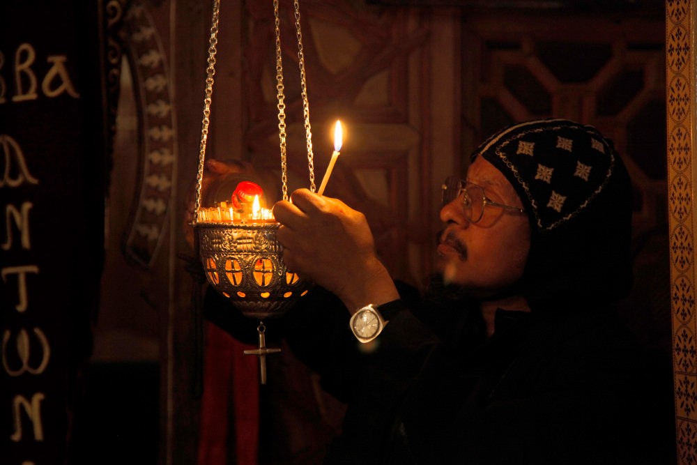 . A monk lights candles during an early morning prayer at the ancient monastery of St. Anthony, southeast of Cairo, Egypt on Wednesday, April 17, 2013. In a cave high in the desert mountains of eastern Egypt, the man said to be the father of monasticism took refuge from the temptations of the world some 17 centuries ago. The monks at the St. Anthony\'s Monastery bearing his name continue the ascetic tradition. But even they are not untouched by the turbulent times facing Egypt\'s Christians, defiantly vowing their community\'s voice won\'t be silenced amid Islamists\' rising power.   (AP Photo/Manoocher Deghati)