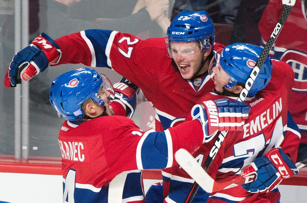 . Montreal Canadiens\' Alex Galchenyuk, center, celebrates with teammates Tomas Plekanec, left, and Alexei Emelin after scoring against the Detroit Red Wings during third period NHL hockey action in Montreal, Tuesday, Oct. 21, 2014. (AP Photo/The Canadian Press, Graham Hughes)