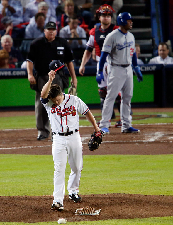 . Atlanta Braves starting pitcher Kris Medlen, bottom, wipes his face after giving up a two-run home run to Los Angeles Dodgers\' Adrian Gonzalez, top right, in the second inning during Game 1 of the National League Divisional Series, Thursday, Oct. 3, 2013, in Atlanta. (AP Photo/Dave Martin)