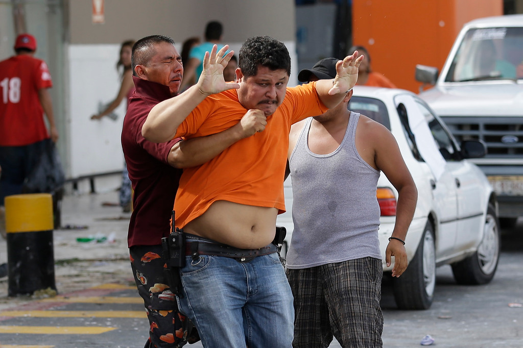 . A man, center in orange, tries to prevent another one from storming a supermarket in Los Cabos, Mexico,  Tuesday, Sept. 16,  2014.  Employees of the supermarket said the company donated all the food at the market and established a system by which every person had 5 minutes to get whatever they could for free as fights broke outside with people inciting the crowd to loot. Desperate locals and tourists were in survival mode in the resort area of Los Cabos also on Wednesday, with electrical and water service still out three days after Hurricane Odile made landfall as a monster Category 3 storm.(AP Photo/Victor R. Caivano)
