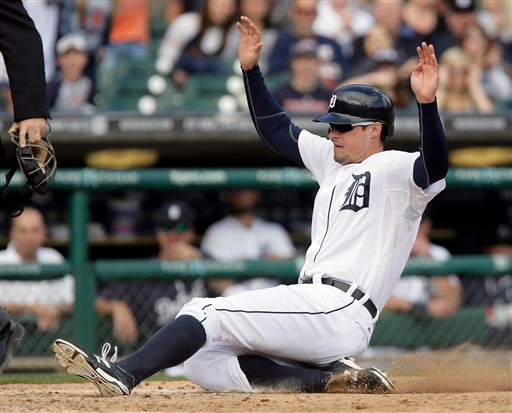 . Detroit Tigers\' Don Kelly slides safely at home to score on a wild pitch by Cleveland Indians\' C.C. Lee, who was trying to intentionally walk Tigers\' Ian Kinsler, during the eighth inning of a baseball game Sunday, Sept. 14, 2014, in Detroit. The Tigers defeated the Indians 6-4. (AP Photo/Duane Burleson)