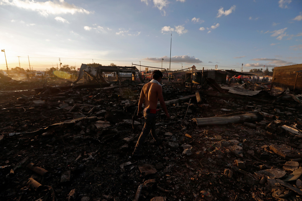 . A man walks  through the scorched ground of the open-air San Pablito fireworks market, in Tultepec, outskirts of Mexico City, Mexico, Tuesday, Dec. 20, 2016.  An explosion ripped through Mexico�s best-known fireworks market on the northern outskirts of the capital Tuesday, injuring scores and killing at least 9 people , according to Mexican Federal Police. (AP Photo/Eduardo Verdugo)