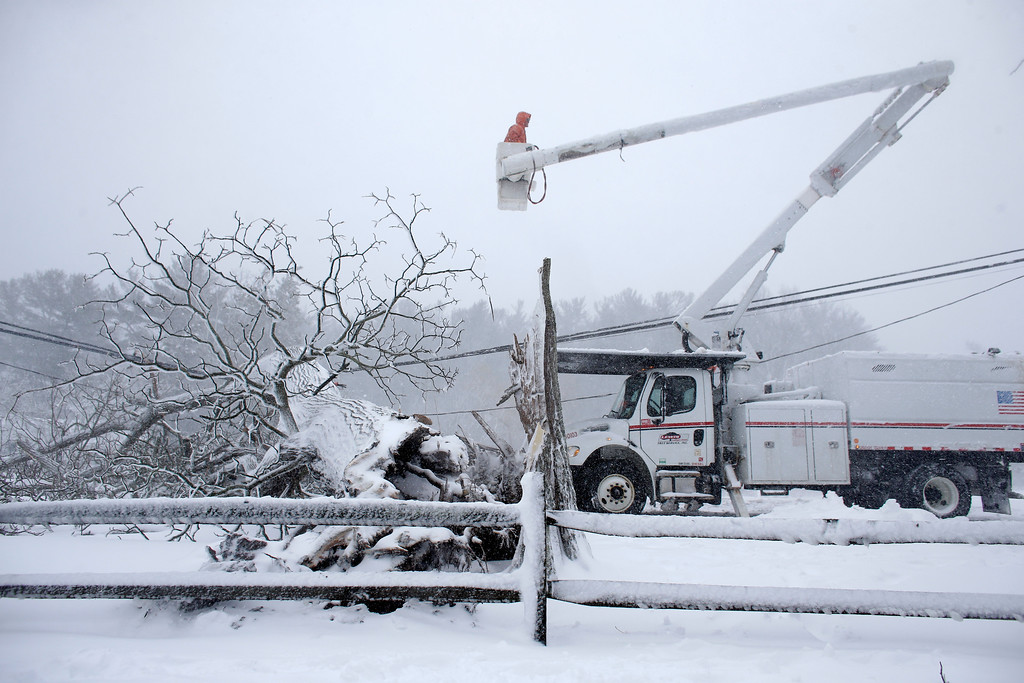 . Workers remove a fallen tree from a road and repair power lines during a winter storm, Tuesday, March 13, 2018 in Norwell, Mass. The nor\'easter is expected to deliver up to 2 feet of snow to some areas of New England. (AP Photo/Steven Senne)