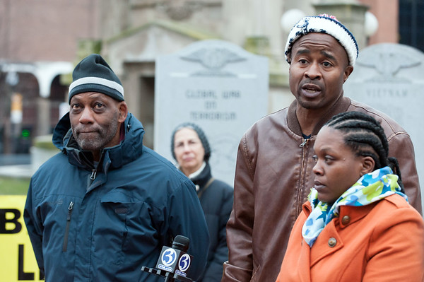 12/14/18 Wesley Bunnell | Staff Activists and family members spoke on Friday afternoon at Central Park, across from city hall, in remembrance of the police involved shooting on Chapman St one year ago. William Tisdol, middle, and Donde Morell, R, parents of Caleb Tisdol who was shot by police speak with the media while standing next to activist Cornell Lewis, L.