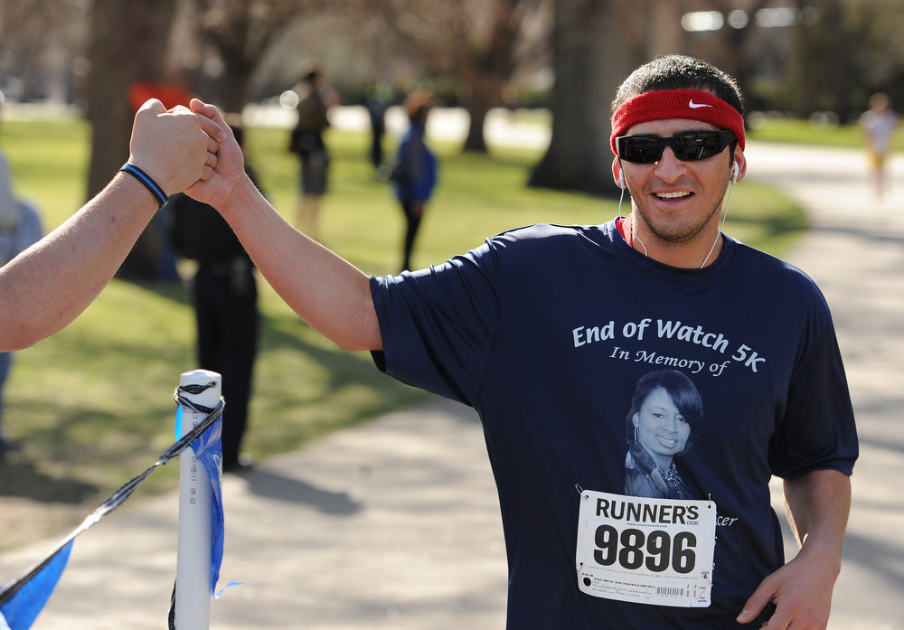 . Marcel Sanchez gets a high five as he finishes the race.  Family, colleagues, and friends of slain Denver Police Officer Celena Hollis turned out April 7, 2013 for a 5k run and walk to raise money for a scholarship fun and a memorial bench in City Park in Denver, CO.  Over 300 runners and walkers participated in the race that started at 9:00 am.  The race looped around City Park.  After the race, a gathering was held to remember Hollis and 22 white doves were released in her memory.  (Photo By Helen H. Richardson/ The Denver Post)