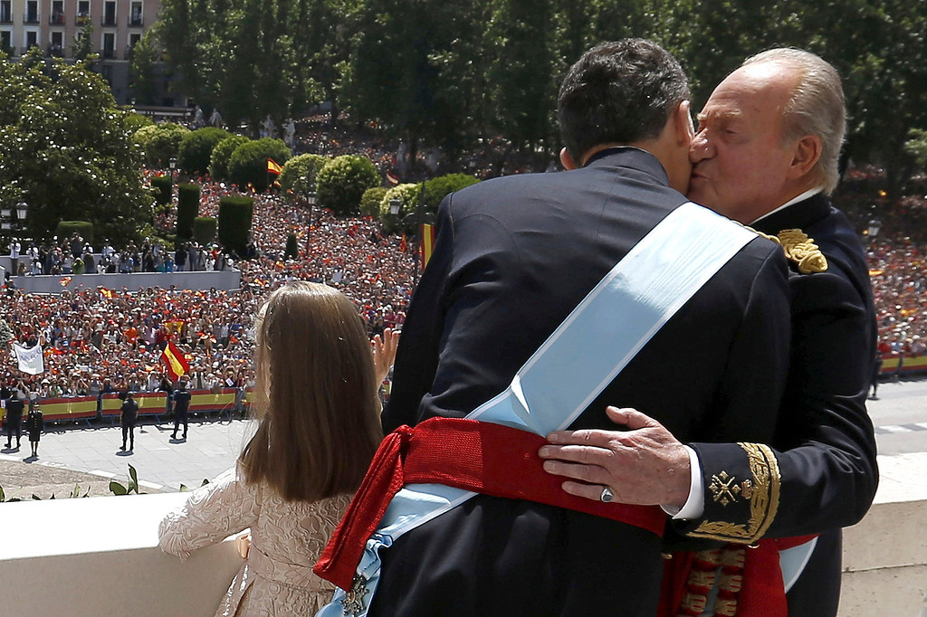 . Spain�s King Juan Carlos, right, kisses his son, the newly crowned King Felipe VI on the balcony of the Royal Palace in Madrid, Spain, on Thursday, June 19, 2014. Spain\'s new King Felipe VI was proclaimed monarch at a formal ceremony in the country\'s Parliament on Thursday, a deliberately low-key occasion for austere times and tarnished royal reputations. (AP Photo/Javier Lizon, Pool)