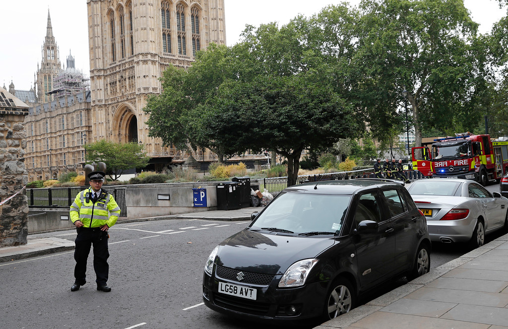 . A police officer stands guard outside the Houses of Parliament, in London, Tuesday, Aug. 14, 2018. London police say that a car has crashed into barriers outside the Houses of Parliament and that there are a number of injured. (AP Photo/Alastair Grant)