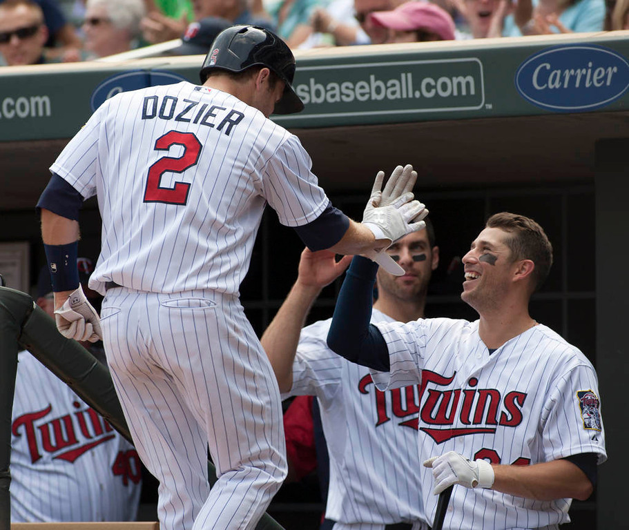 . Minnesota Twins\' Brian Dozier  is congratulated by teammate Trevor Plouffe, right, after scoring from second on a Josh Willingham double during the third inning. (AP Photo/Paul Battaglia)