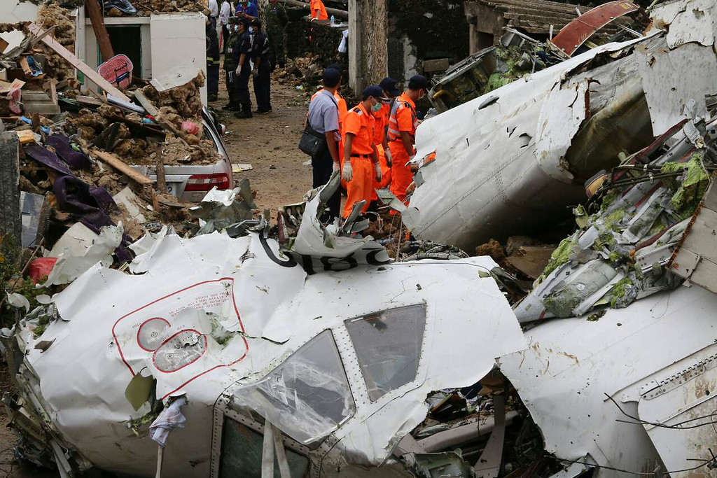. Rescue workers survey the wreckage of TransAsia Airways Flight GE222 on the Taiwanese island of Penghu Thursday, July 24, 2014.(AP Photo) TAIWAN OUT