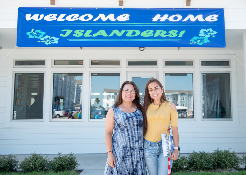Corrie Canul (right) and her mom pose in front of the Momentum Village Clubhouse after checking in during the Mometum Village Move-In Day.