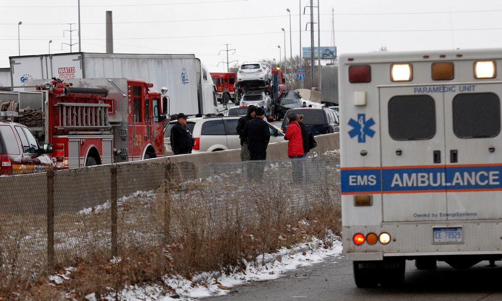 ". First responders and police officers shut down a freeway due to an accident involving multiple cars and semi-trucks in Detroit, Michigan January 31, 2013. Three people were killed and roughly two dozen injured in a series of crashes involving 30 to 40 vehicles in ""white-out\"" conditions along a slippery stretch of highway in Detroit, state police said on Thursday. REUTERS/Rebecca Cook"