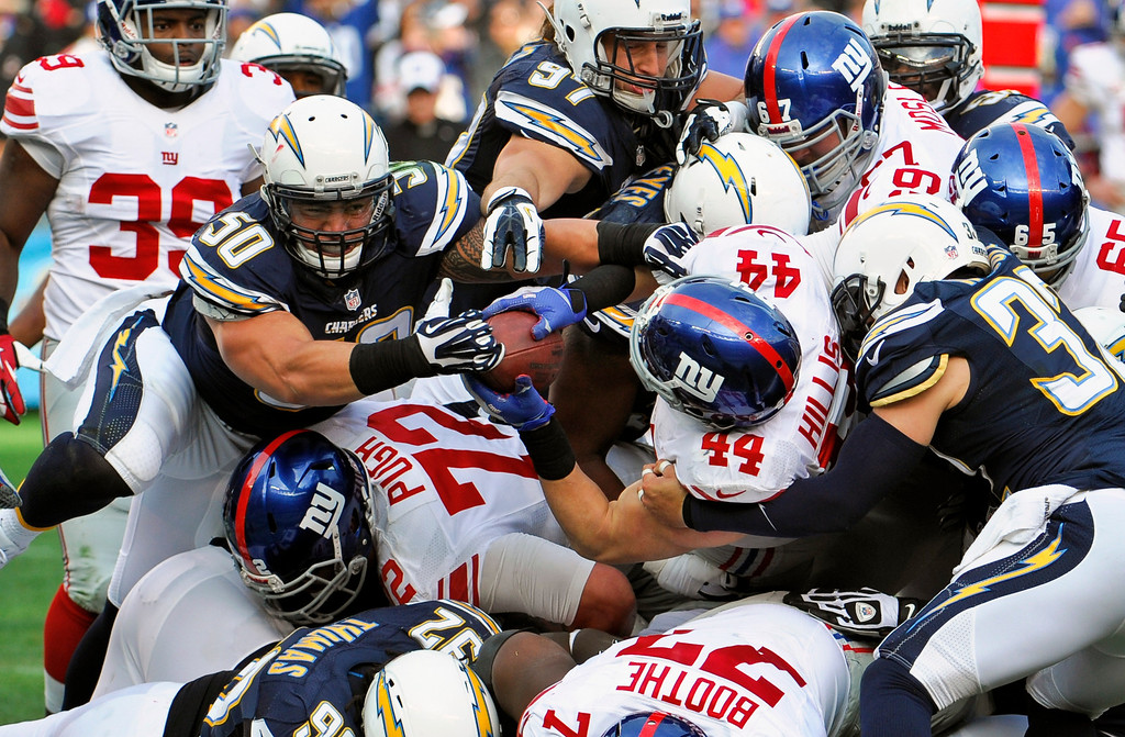 . New York Giants running back Peyton Hillis carries the ball into the end zone while San Diego Chargers linebacker Manti Te\'o attempts to take the ball away on a 1-yard touchdown run during the second half of an NFL football game on Sunday, Dec. 8, 2013, in San Diego. (AP Photo/Denis Poroy)