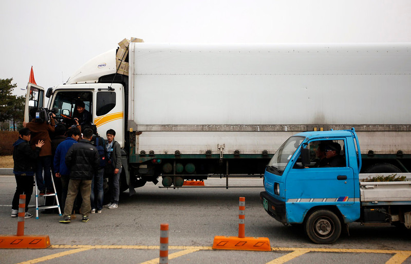 . A South Korean truck driver (L) returning from the Kaesong Industrial Complex (KIC) inside the North Korean border, answers reporters\' questions upon his arrival at the South\'s CIQ (Customs, Immigration and Quarantine), just south of the demilitarized zone separating the two Koreas, in Paju, north of Seoul, April 8, 2013. Movement around an atomic test site in North Korea indicates the reclusive state may stage another nuclear test, a South Korean minister said on Monday, an act that would further drive up tensions on the Korean peninsula.   REUTERS/Kim Hong-Ji