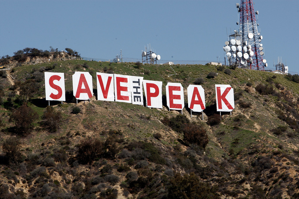 ". The famous sign that normally spells ""Hollywood\"" has been draped with new lettering to say \""Save The Peak,\"" a reference to nearby Cahuenga Peak, that has been the object of developer interest, seen in the Hollywood Hills above Los Angeles Saturday, Feb. 13, 2010.  The new temporary signage seeks donations so the city can purchase land adjacent to the Hollywood Sign, keeping the famous view clear of real estate development.  (AP Photo/Reed Saxon)"