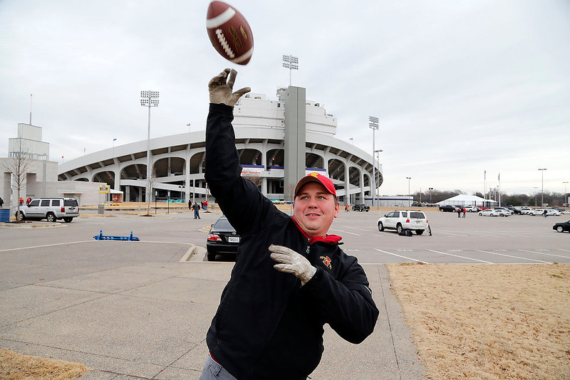 . Iowa State fan Trent Ragaller throws a football while tailgating before the Liberty Bowl NCAA college football game between Iowa State and Tulsa, Monday, Dec. 31, 2012, in Memphis, Tenn. (AP Photo/The Des Moines Register, David Purdy)