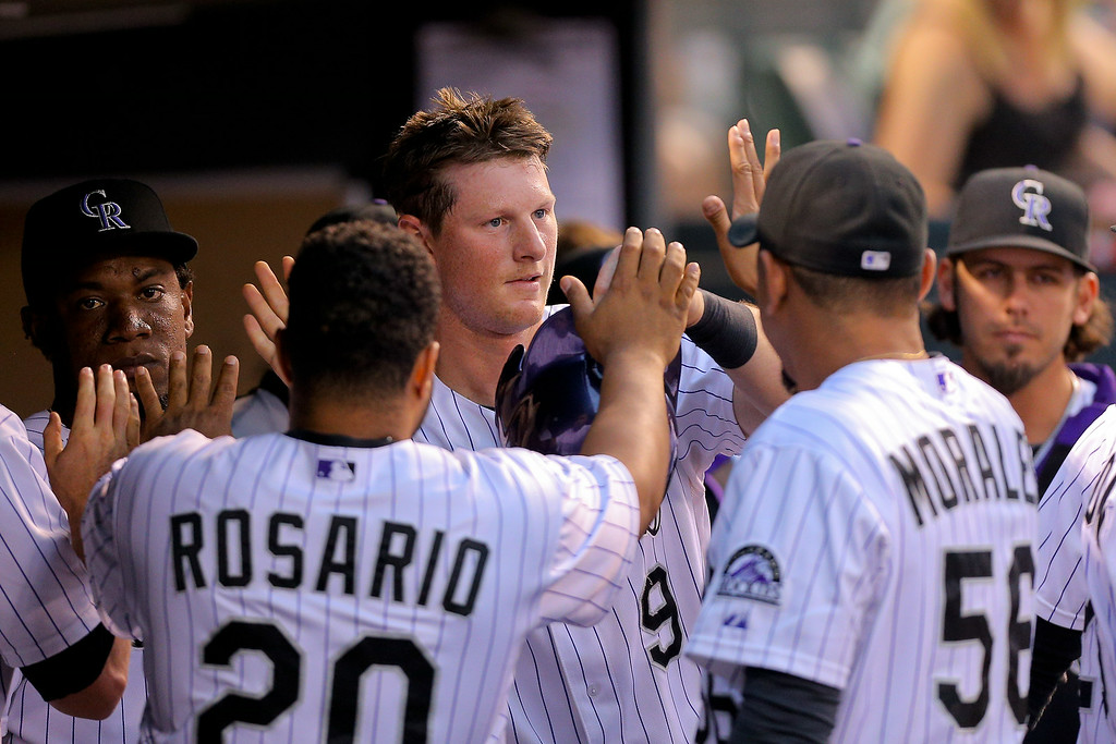 . DJ LeMahieu #9 of the Colorado Rockies is greeted in the dugout after scoring during the third inning against the Pittsburgh Pirates at Coors Field on July 25, 2014 in Denver, Colorado. (Photo by Justin Edmonds/Getty Images)