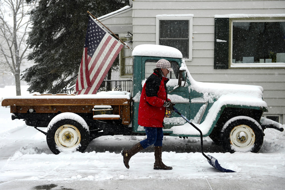 . Nikki Maloney shovels snow in front of a 1962 Willys truck at her home on Monroe in south Denver. Snow is expected to fall throughout the day. (Photo by AAron Ontiveroz/The Denver Post)