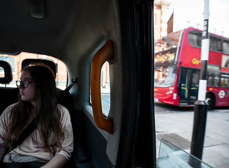 Young woman travelling by taxi in London.  London, England, 2018.