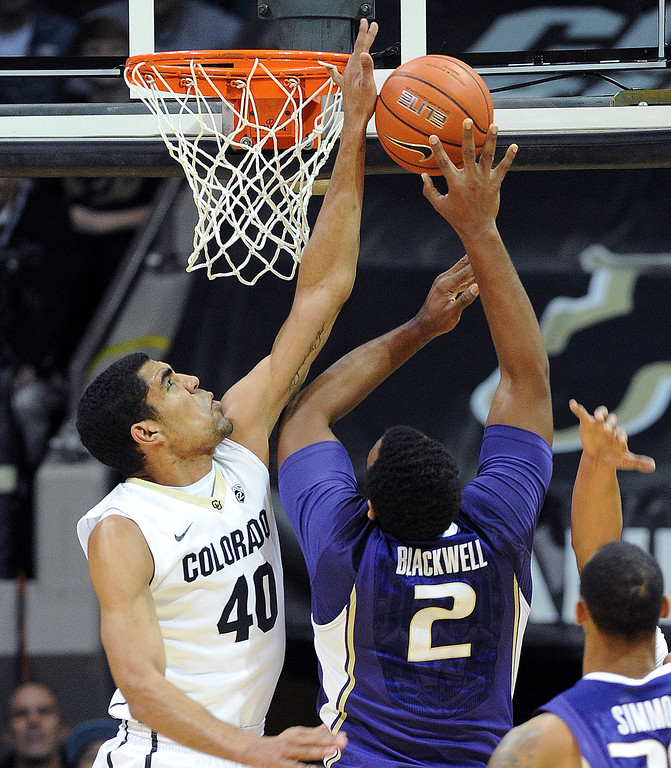 . Colorado\'s Josh Scott, left, blocks the shot of Perris Blackwell of Washington, during the first half of an NCAA college basketball game in Boulder, Colo., Sunday, Feb. 9, 2014. (AP Photo/Daily Camera, Cliff Grassmick)