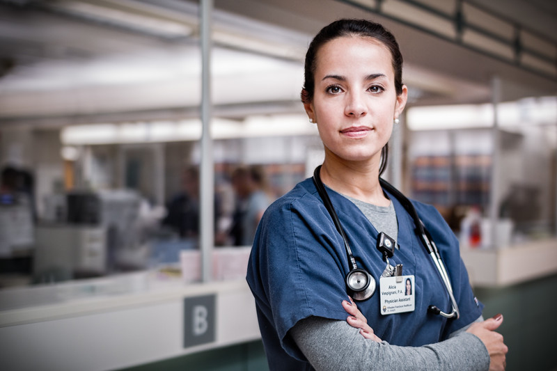 Portrait of Confident Female Nurse in Blue Scrubs  at Nursing Station
